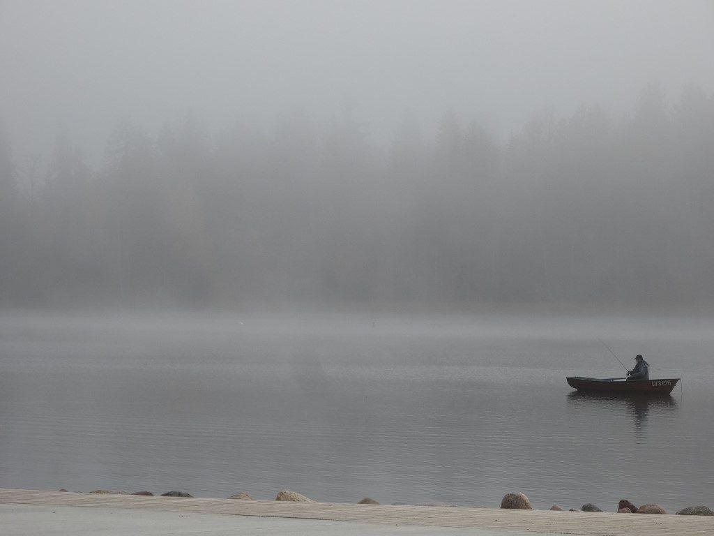Un pêcheur dans la brume matinale sur le lac