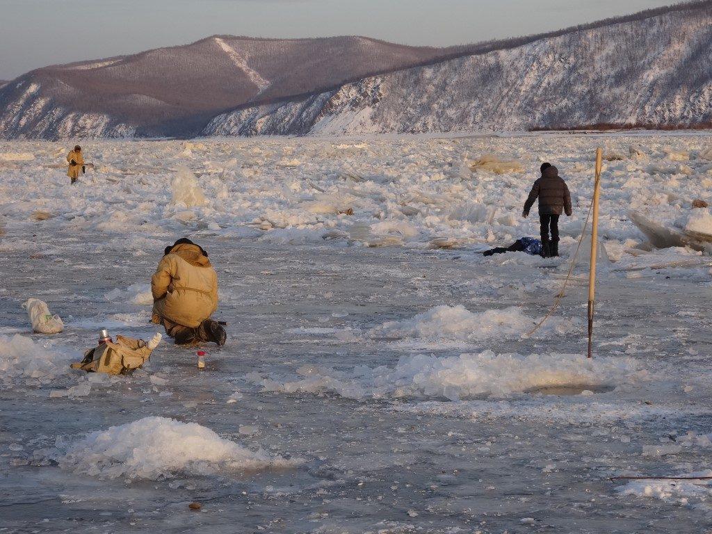 Les pêcheurs dans la glace sur la rive gelée du fleuve Amour