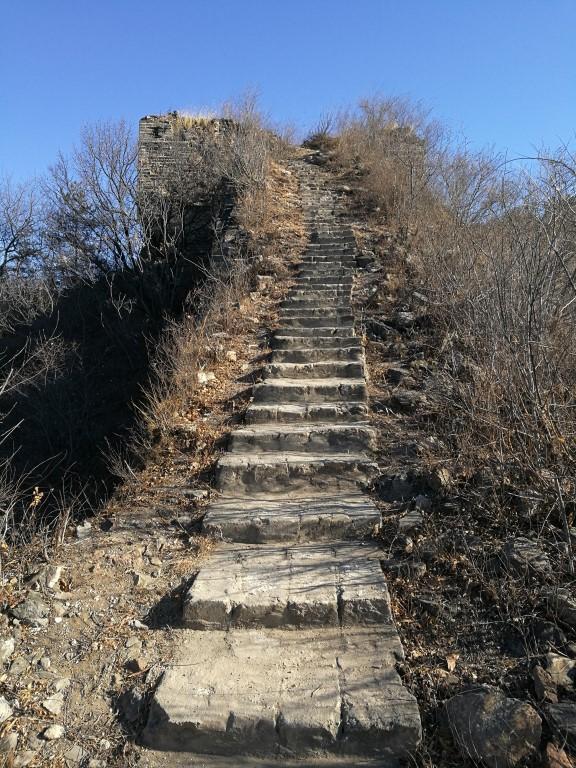 Un escalier qui monte le long de la crête de la montagne vers une tour de la grande muraille