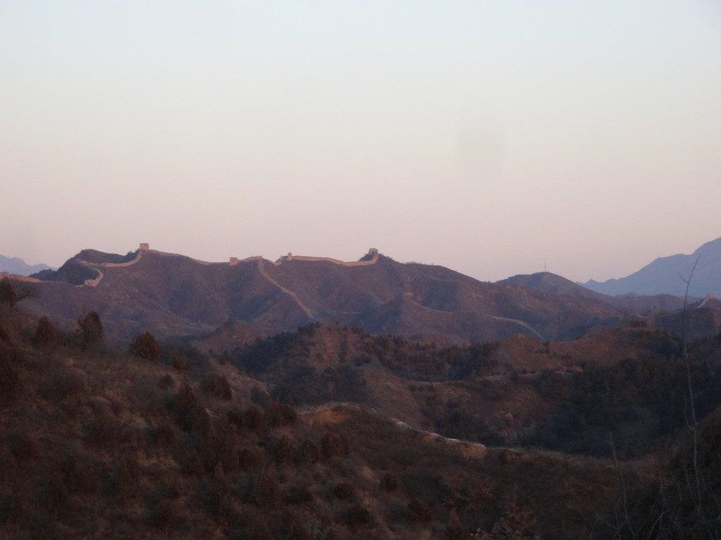 Au coucher du soleil, la Grande Muraille qui se déroule à l'horizon
