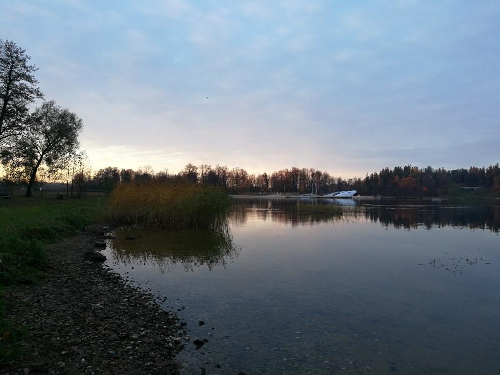 Le coucher du soleil sur le lac depuis une petite plage de galets